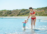 Mother and baby girl running on sea coast