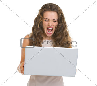 Angry young woman yelling on laptop