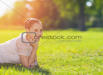 Smiling girl laying on meadow and looking on copy space