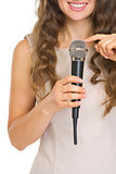 Closeup on young woman tapping on microphone to check sound