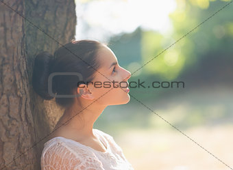 Thoughtful girl leaning on tree and looking on copy space