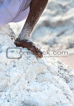Bare worker foot salt in salt farm