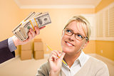 Woman Being Handed Stacks of Money in Empty Room