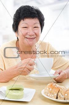 Asian senior woman having breakfast