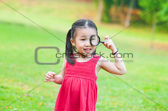 Little Asian girl with magnifier glass