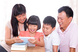  Parents and children using tablet pc together.