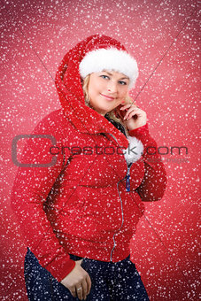 Joyful pretty woman in red santa claus hat smiling with snowflakes
