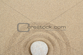 zen stone in sand with circles