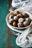 Bowl of quail&#39;s eggs on old painted table