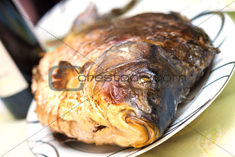 Baked carp in a plate with wine in background