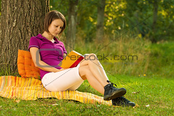 Beautiful young brunette reading in the park