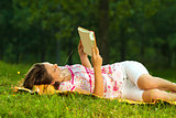 Beautiful young brunette reading on a meadow in the park