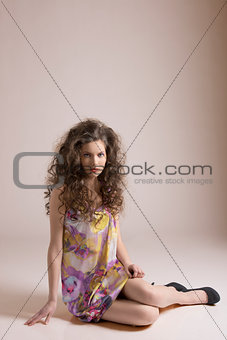 pretty girl sitting on a floor with hand on the floor