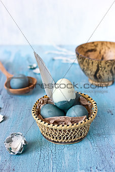 Still life with blue easter eggs in a wattled plate