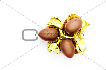 Three chocolate eggs on a golden foil