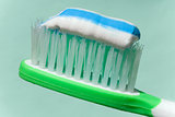 close up view of toothbrush and some toothpaste on it on green b
