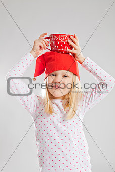 Happy young girl holding big cup on head
