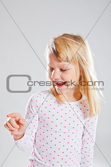 Happy smiling young girl pointing