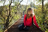 Woman hiking resting on the suspension bridge