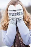 Girl in winter clothes covered her face with wool mittens
