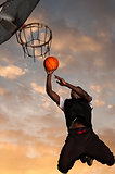 One young man playing basketball in park