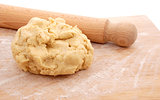 Wooden rolling pin and a fresh ball of pastry on a floured board