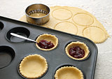 Cutting and filling pastry shapes to make jam tarts 