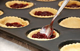 Closeup of jam tarts being filled with a teaspoon