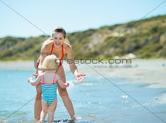 Mother and baby girl playing on sea coast