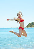Happy young woman jumping at seaside