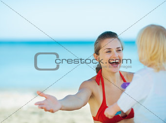 Happy mother playing with baby girl on beach