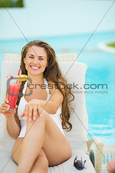 Portrait of smiling young woman laying on sunbed and enjoying co