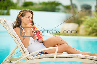 Happy young woman laying on sunbed and drinking cocktail