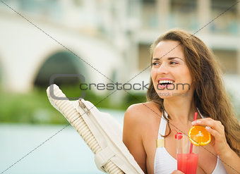 Happy young woman with cocktail looking on copy space