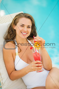 Happy young woman laying on sunbed enjoying cocktail at poolside