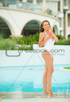 Happy young woman enjoying cocktail at poolside