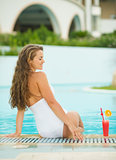 Happy young woman sitting at pool with cocktail
