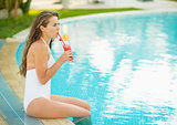 Happy young woman sitting at pool and drinking cocktail