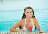 Portrait of happy young woman at pool with cocktail