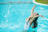 Happy young woman splashing water in pool