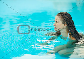 Portrait of young woman in pool looking on copy space