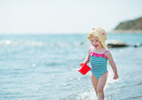 Happy baby running along sea shore