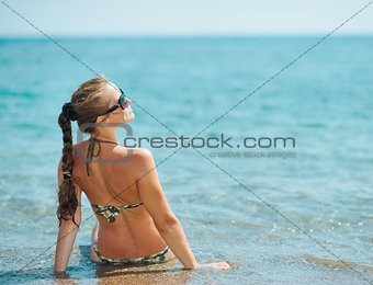 Young woman sitting on sea coast. rear view