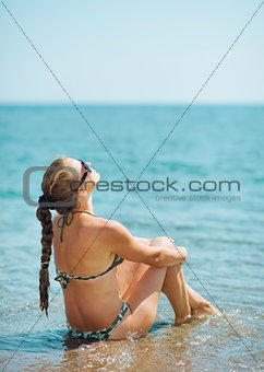 Young woman relaxing at seaside. rear view