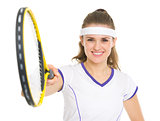 Smiling tennis player pointing racket in camera