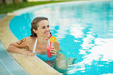 Happy young woman at pool with cocktail looking on copy space