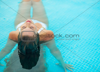 Young woman relaxing in pool. rear view
