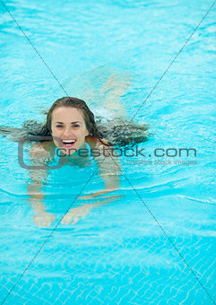 Happy young woman swimming in pool