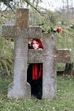 Gothic girl with a rose on a cemetery