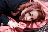 Closeup of a redhead girl in with red satin cloak